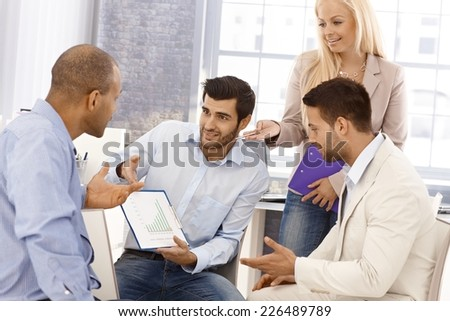Young businesspeople sitting in office, working together, discussing business diagram. - stock photo