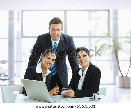 Young businesspeople talking in office lobby, looking at camera, smiling.