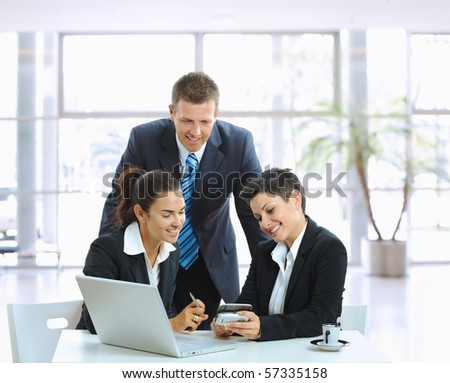 Young businesspeople talking in office lobby, looking at smart mobile phone, smiling. - stock photo