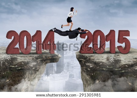 Young businesspeople try through a gap with cooperation from number 2014 to 2015 - stock photo