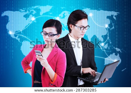 Young businesspeople using laptop computer and mobile phone to communicate with their partners