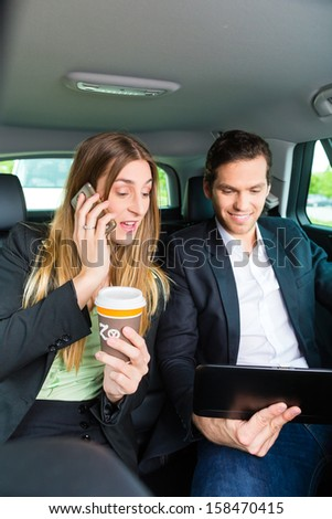 Young businesspeople with mobile phone and tablet computer traveling in taxi, they are colleagues