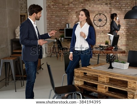 Young businesspeople working in startup office, talking, using tablet. - stock photo