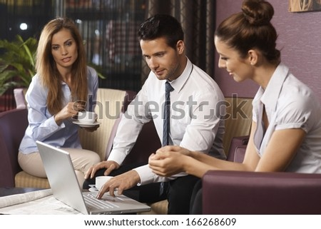 Young businesspeople working late on laptop computer sitting in hotel lobby or bar, drinking coffee. - stock photo
