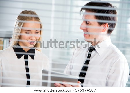 Young businesspeople working on a tablet computer at the office blinds. - stock photo