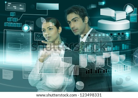 young businesspeople working on futuristic virtual screen - stock photo