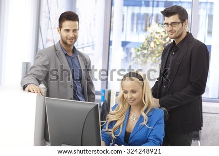Young businesspeople working together in bright office, using computer. - stock photo