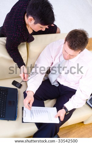 Young businesspeople working together, sitting at couch in office. Overhead shot.