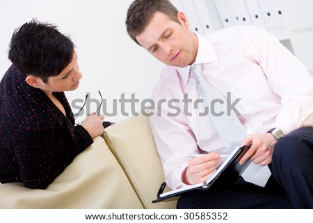 Young businesspeople working together, sitting on couch. Discussing notes in personal organizer. - stock photo