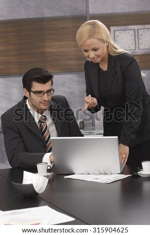 Young businesspeople working together, using laptop computer. - stock photo