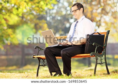 Young businessperson sitting on a bench and working on a laptop in a park - stock photo