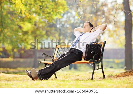 Young businessperson sitting on a wooden bench and relaxing in a park - stock photo