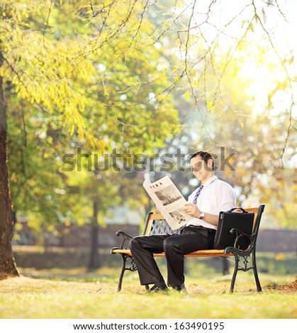 Young businessperson sitting on a wooden bench and working on a laptop in a park, shot with a tilt and shift - stock photo