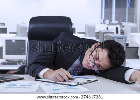 Young businessperson sleeping in the office with paperwork on the table - stock photo