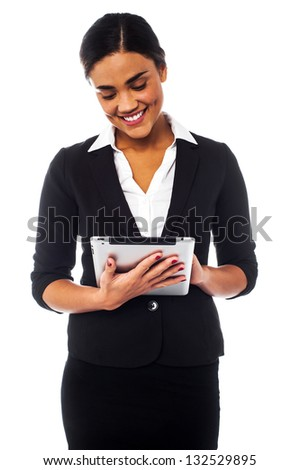 Young businesswoman accessing tablet pc and browsing internet on it. - stock photo