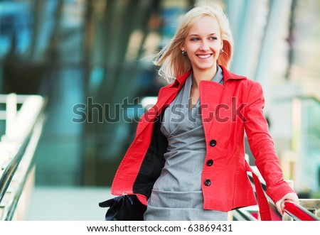 Young businesswoman against office windows. - stock photo