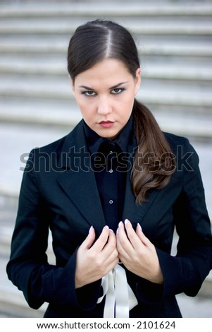 Young businesswoman, against some stairs, dead-serious, focus on her lips