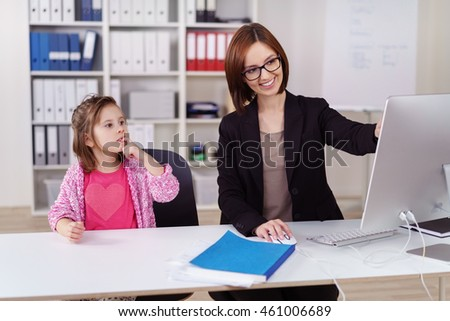 Young businesswoman amusing her small daughter as she babysits her in the office smiling as she shows her something on the computer screen