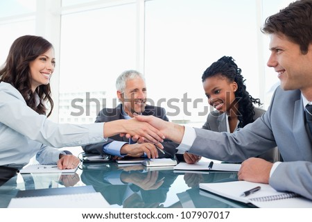 Young businesswoman and a co-worker shaking hands during a meeting