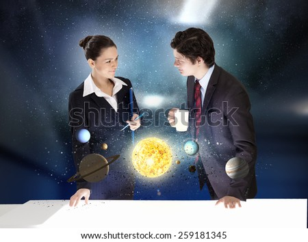 Young businesswoman and businessman and planets of space spinning around - stock photo