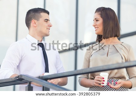 Young businesswoman and businessman having a coffee break in front of their office. They are looking at each other, talking and drinking coffee. - stock photo