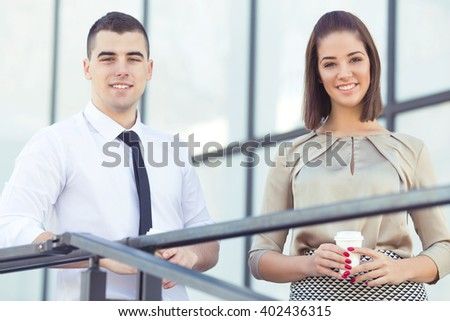 Young businesswoman and businessman having a coffee break in front of their office. They are looking at camera, smiling and drinking coffee. - stock photo