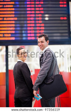 young businesswoman and businessman in front of airport information board - stock photo