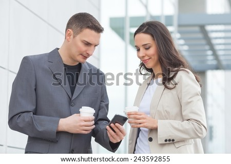 Young businesswoman and businessman on the coffee break looking at mobile phone - stock photo