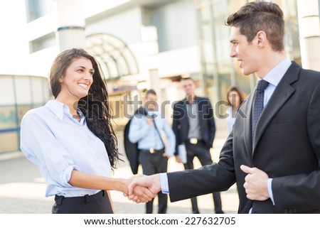 Young businesswoman and businessman shaking hands in front of the company while in the background them watching the rest of the business team.