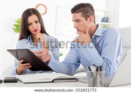 Young businesswoman and businessman, sitting in the office at an office desk with a serious expression on their faces look in the folder that holds a business woman. - stock photo
