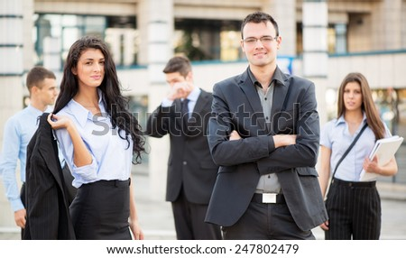 Young businesswoman and businessman, with their team in the background, standing in front of office building, with a smile looking at camera. - stock photo