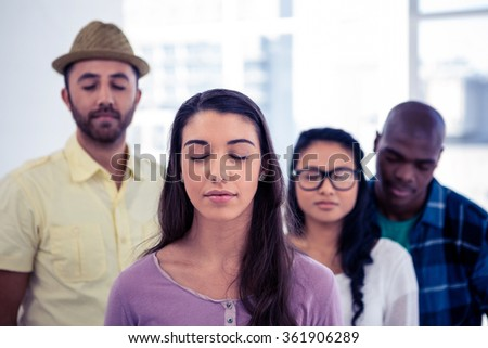 Young businesswoman and team with eyes closed in creative office - stock photo