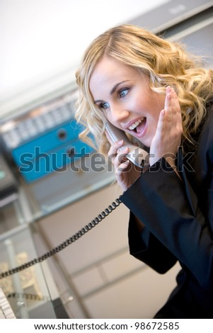 young businesswoman answering phone with surprised facial expression - stock photo
