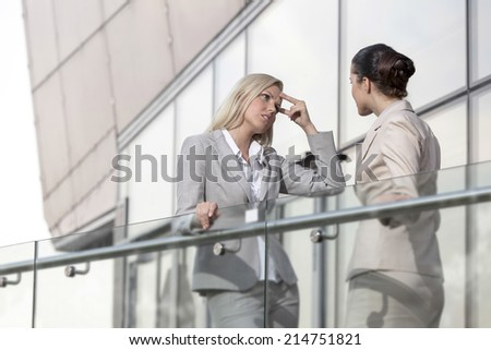 Young businesswoman arguing with female colleague at office railing - stock photo