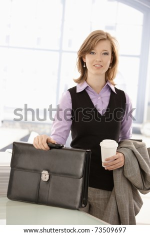 Young businesswoman arrived to office in the morning with coffee to go in hand. - stock photo