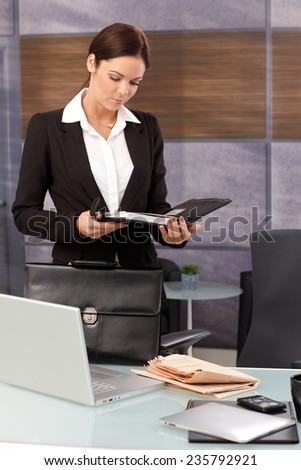 Young businesswoman arriving at office, looking at daily tasks in organizer. - stock photo