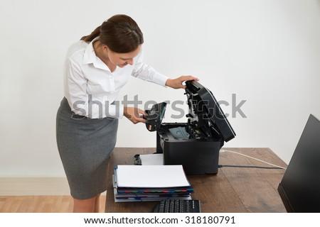 Young Businesswoman At Desk Putting Laser Toner Cartridge In Printer - stock photo