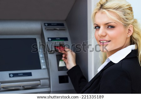 Young businesswoman at the ATM - stock photo