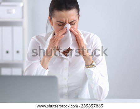 Young businesswoman blowing her nose, sits at her desk, isolated - stock photo