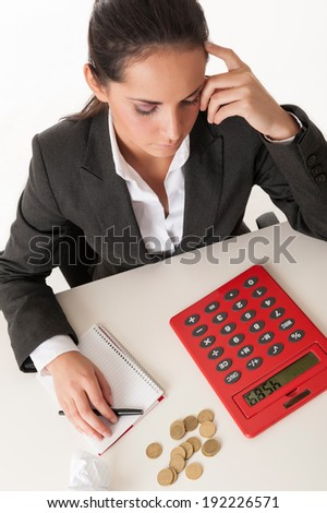 Young businesswoman calculating savings against white background. - stock photo