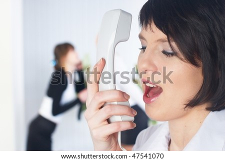 Young businesswoman calling by phone in office