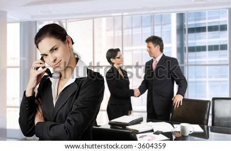Young businesswoman calls on cell phone while other business people are shaking hands in the background. Daylight, indoor, office.