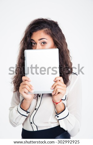 Young businesswoman covering her face with tablet computer and looking at camera isolated on a white background - stock photo