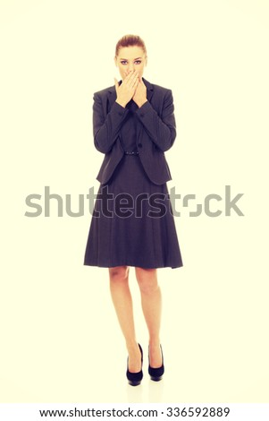 Young businesswoman covering mouth with hands. - stock photo