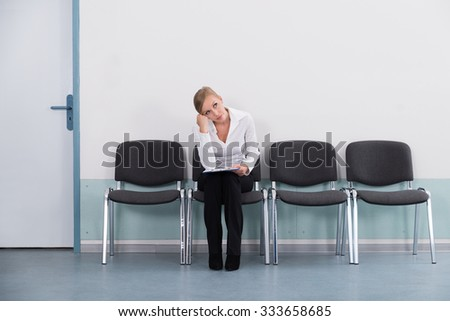 Young Businesswoman Daydreaming While Sitting On Chair - stock photo