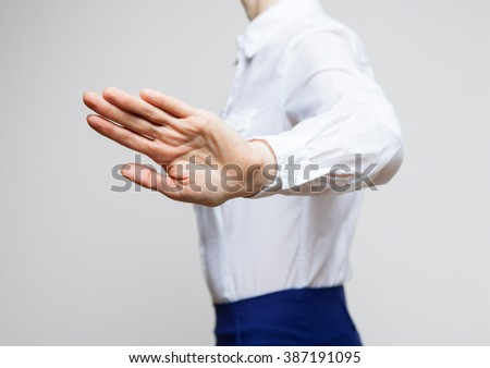 Young businesswoman demonstrating prohibiting gesture, neutral background - stock photo
