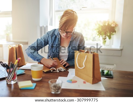 Young businesswoman designing packaging for her new start-up online business sitting at her desk at home working on a gift bag - stock photo