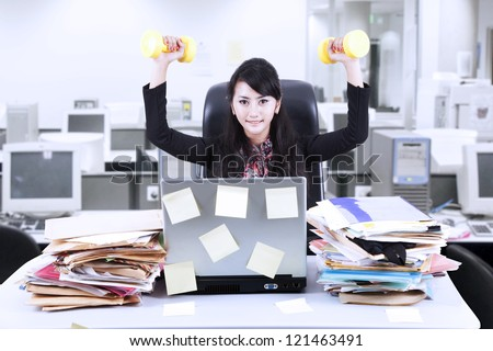 Young businesswoman doing exercise in front of her laptop with lots of sticky notes - stock photo