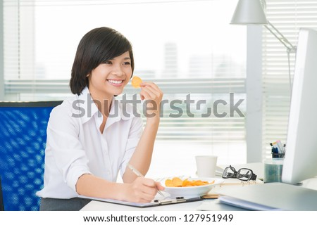 Young businesswoman doing paperwork and eating crisps - stock photo