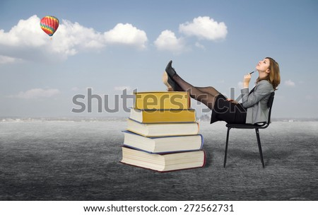 Young businesswoman dreaming sitting on a chair in the open air.